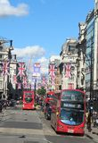 Flags and red London buses in Oxford Street London Royalty Free Stock Images