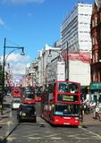 Flags and red London buses in Oxford Street London Royalty Free Stock Photography