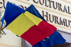 Flags of the Romania and European Union waving in the breeze on the wall of administrative building. Flags of the Romania and European Union waving in the breeze Royalty Free Stock Photography