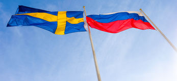 Flags of Russia and Sweden against blue sky. Flags of Russia and Sweden waving against blue sky royalty free stock photos