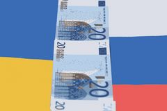 Between the flags of Russia and Ukraine are banknotes of 20 Euro. Concept : Russia and Ukraine have divided European Union money Royalty Free Stock Photo