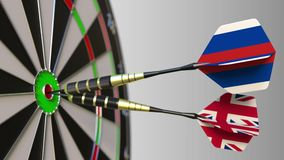 Flags of Russia and the United Kingdom on darts hitting bullseye of the target. International cooperation or competition. Animation stock footage