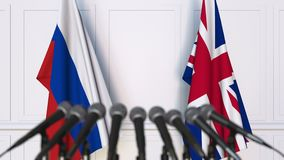 Flags of Russia and The United Kingdom at international meeting or negotiations press conference. 3D animation stock footage