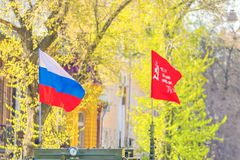 Flags of the Russian Federation victory develops on the background of trees. Spring sunny day stock image