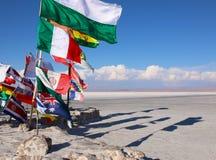 Flags in a salt desert of Salar de Uyuni in Bolivia stock photo