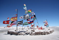 Flags in a salt desert of Salar de Uyuni Stock Photo