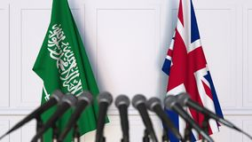 Flags of Saudi Arabia and The United Kingdom at international meeting or negotiations press conference. 3D animation stock video