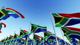 Flags of South Africa on flag poles against blue sky. stock video footage