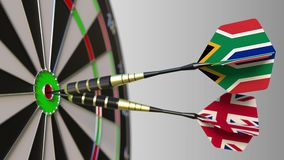 Flags of South Africa and the United Kingdom on darts hitting bullseye of the target. International cooperation or. Competition animation stock video