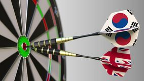 Flags of South Korea and the United Kingdom on darts hitting bullseye of the target. International cooperation or. Competition animation stock footage