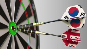 Flags of South Korea and the United Kingdom on darts hitting bullseye of the target. International cooperation or. Competition Royalty Free Stock Photography