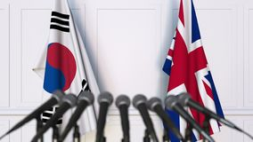 Flags of South Korea and The United Kingdom at international meeting or negotiations press conference. 3D animation stock footage