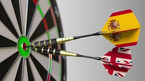 Flags of Spain and the United Kingdom on darts hitting bullseye of the target. International cooperation or competition. Animation stock video