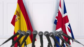 Flags of Spain and The United Kingdom at international meeting or negotiations press conference. 3D animation stock video footage