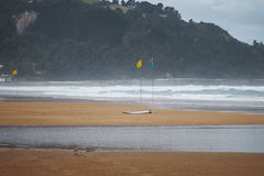 Flags and a surfboard on  beach Stock Images