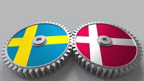 Flags of Sweden and Denmark on meshing gears. International cooperation conceptual animation stock video footage