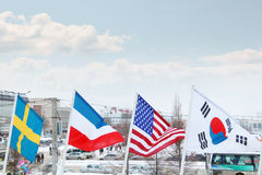 Flags of Sweden, Luxembourg, USA, South Korea on wind. At winter cloudy day in street of city Stock Photography