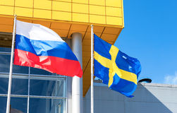 Flags of Sweden and Russia waving against IKEA store. SAMARA, RUSSIA - JUNE 14, 2015: Flags of Sweden and Russia waving against IKEA store royalty free stock image