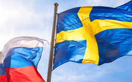 Flags of Sweden and Russia waving against sky. Flags of Sweden and Russia waving against blue sky Stock Image