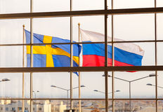 Flags of Sweden and Russia waving against windows. Of store stock photo
