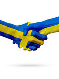 Flags Sweden, Ukraine countries, partnership friendship handshake concept. Flags Sweden, Ukraine countries, handshake cooperation, partnership, friendship or Stock Photo