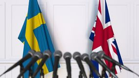 Flags of Sweden and The United Kingdom at international meeting or negotiations press conference. 3D animation stock video footage