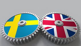 Flags of Sweden and The United Kingdom on meshing gears. International cooperation conceptual animation. Flags of Sweden and The United Kingdom on meshing gears stock video