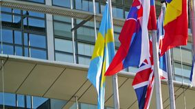 Flags of Sweden, United Kingdom, Romania,Slovakia,  Finland waving in front of Parliament, Strasbourg stock video