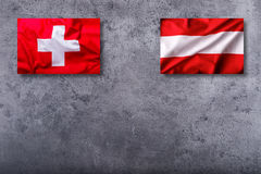 Flags of the switzerland and austria on concrete background Royalty Free Stock Photo