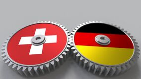 Flags of Switzerland and Germany on meshing gears. International cooperation conceptual animation. Flags of Switzerland and Germany on meshing gears stock footage
