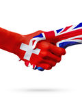 Flags Switzerland, United Kingdom countries, partnership friendship handshake concept. Stock Images