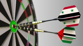 Flags of Syria and the UAE on darts hitting bullseye of the target. International cooperation or competition conceptual. Flags of Syria and the UAE on darts stock video footage