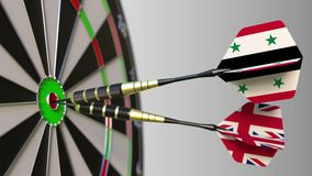 Flags of Syria and the United Kingdom on darts hitting bullseye of the target. International cooperation or competition. Animation stock video footage