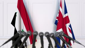 Flags of Syria and The United Kingdom at international meeting or negotiations press conference. 3D animation stock video