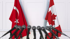Flags of Turkey and Canada at international meeting or negotiations press conference. 3D animation stock footage