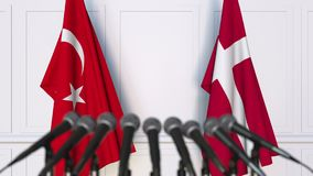 Flags of Turkey and Denmark at international meeting or negotiations press conference. 3D animation stock footage