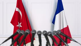 Flags of Turkey and France at international meeting or negotiations press conference. 3D animation stock footage