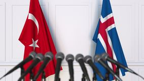 Flags of Turkey and Iceland at international meeting or negotiations press conference. 3D animation stock footage
