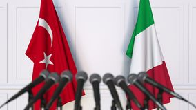 Flags of Turkey and Italy at international meeting or negotiations press conference. 3D animation stock footage