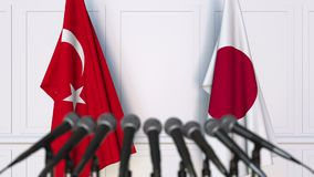 Flags of Turkey and Japan at international meeting or negotiations press conference. 3D animation stock video footage