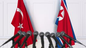 Flags of Turkey and North Korea at international meeting or negotiations press conference. 3D animation stock footage