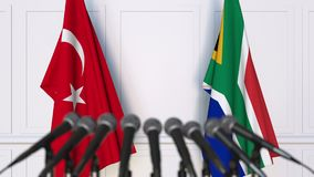 Flags of Turkey and South Africa at international meeting or negotiations press conference. 3D animation stock footage