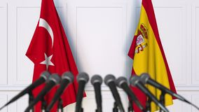 Flags of Turkey and Spain at international meeting or negotiations press conference. 3D animation stock video