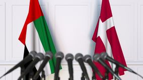 Flags of the UAE and Denmark at international meeting or negotiations press conference. 3D animation stock video
