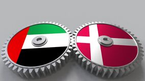 Flags of the UAE and Denmark on meshing gears. International cooperation conceptual animation stock footage