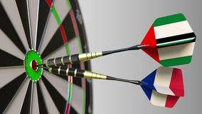 Flags of the UAE and France on darts hitting bullseye of the target. Flags of the UAE and France on darts hitting bullseye stock footage