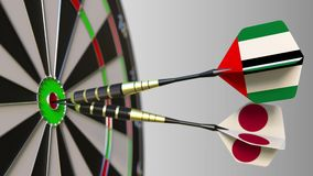 Flags of the UAE and Japan on darts hitting bullseye of the target. International cooperation or competition conceptual. Flags of the UAE and Japan on darts stock video footage