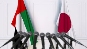 Flags of the UAE and Japan at international meeting or negotiations press conference. 3D animation stock video