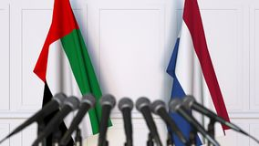 Flags of the UAE and Netherlands at international meeting or negotiations press conference. 3D animation stock video