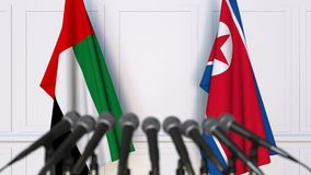 Flags of the UAE and North Korea at international meeting or negotiations press conference. 3D animation stock footage